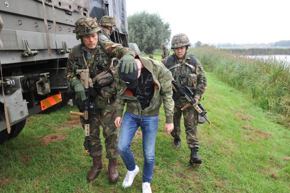 Een van de jonge relschoppers die bij het Heemskerkse Luchtoorlogmuseum Fort Veldhuis voor gespeelde onrust zorgden, wordt afgevoerd.