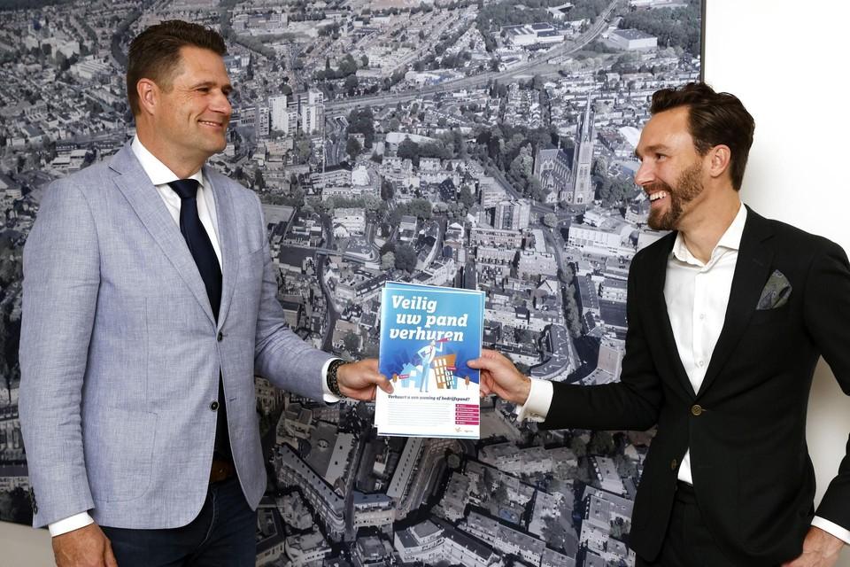 Wethouder Arno Scheepers (rechts) overhandigt de brochure 'Veilig uw pand verhuren' aan Jeroen Jones.