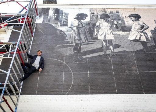 Sidney Waerts beschildert blinde muur in Haarlemse Johan van Vlietstraat: Meisjes maken hun eigen heelal