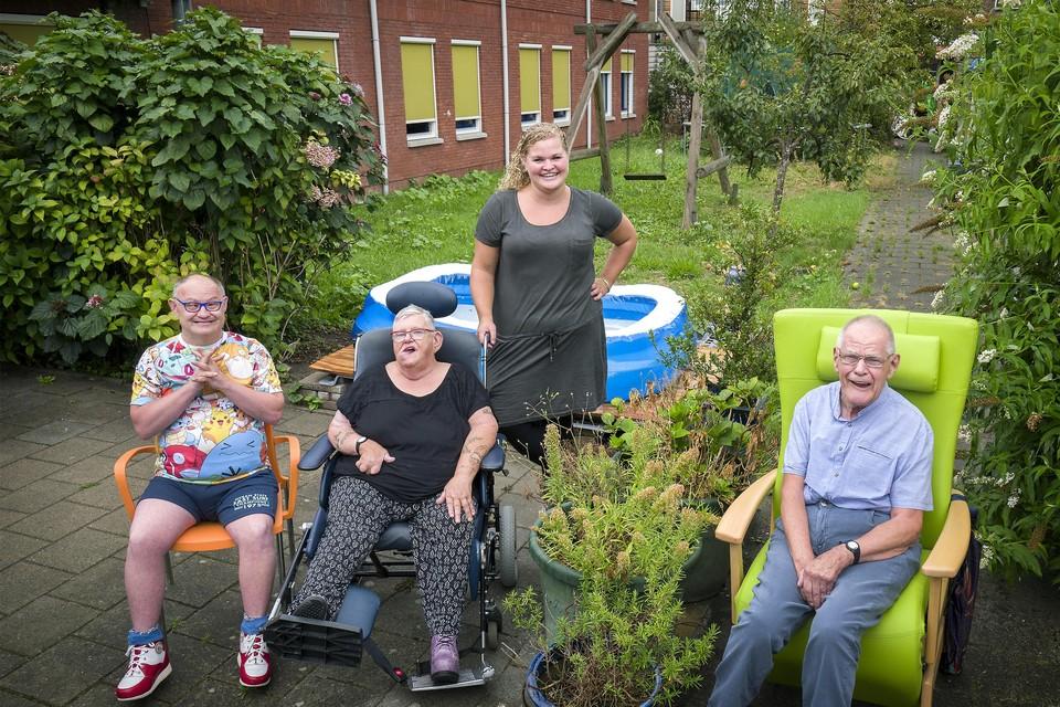 Bewoners Rob, Bep en Henk met begeleider Fabienne in de tuin die opgeknapt moet worden.