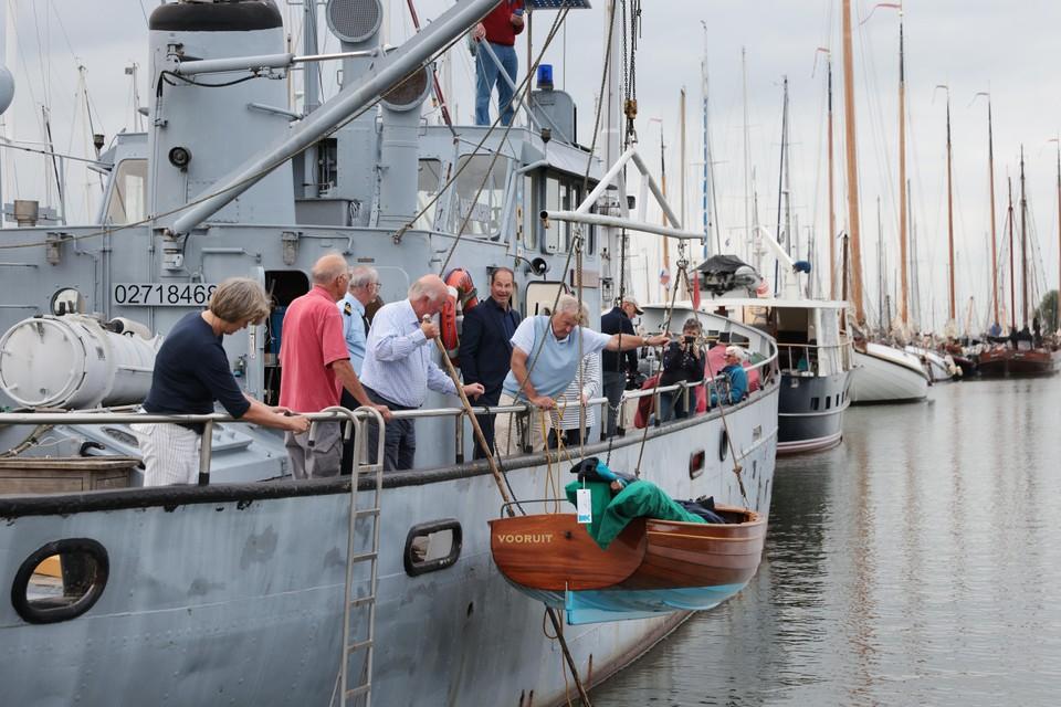 Met een hijskraan worden de jollen aan boord van de Waddenzee gehesen.
