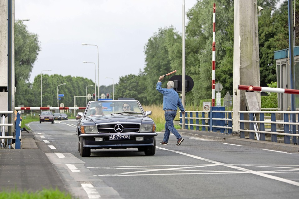 De brugwachter regelt het verkeer zonder bescherming van een reflecterend hesje.