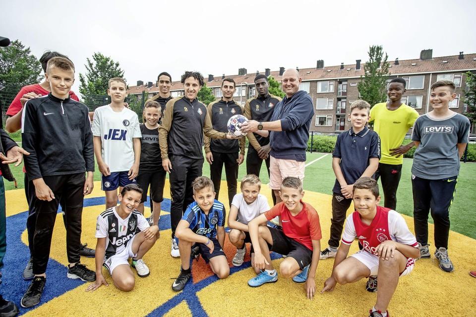 Telstar-spelers overhandigen wedstrijdbal aan buurtsportcoach Andres (staand vierde van rechts) en kids op het Cruijff Court.