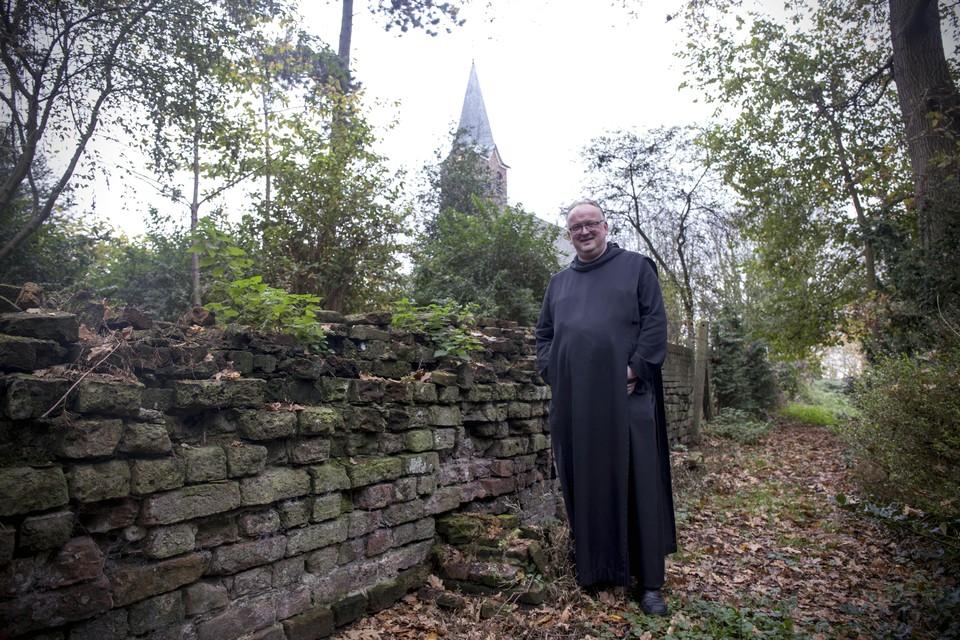 Broeder Adelbert naast het enig overgebleven stuk muur van de middeleeuwse abdij. Gezien de leeftijd van de kloostermoppen moet deze muur hier in 1245 al gestaan hebben.