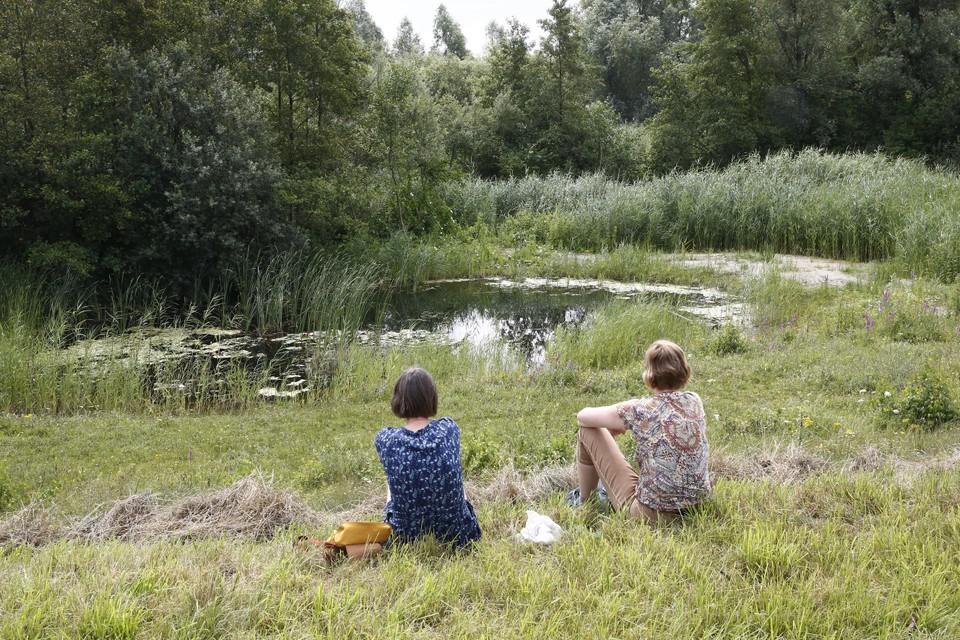 Twee wandelaars die natuurgebied Stichtse Brug hebben weten te vinden rusten uit bij een van de waterpartijen.
