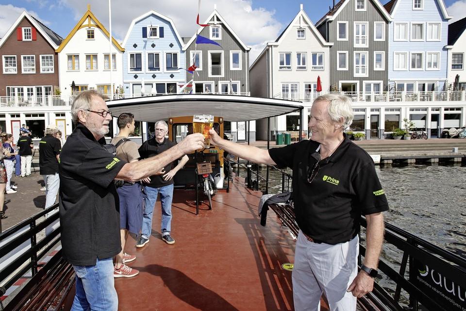 Hennephof (links) en voorzitter Van de Weert proosten op het verbouwde fietsveer. Medebouwer Van Maanen kijkt op de achtergrond toe.