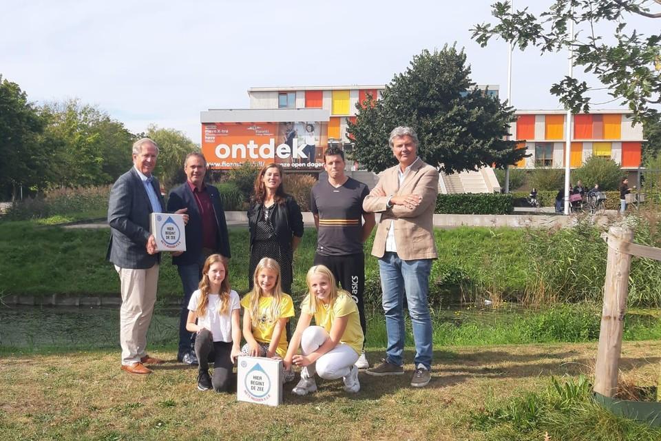 Jan Boot van Rotaryclub Lisse Bollenstreek (links) en wethouder Jan van Rijn (tweede van links) tonen in gezelschap van enkele docenten en leerlingen van het Fioretti College Hillegom de tegels.