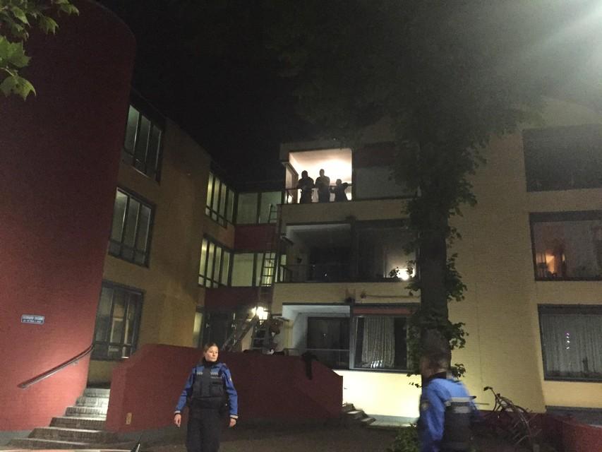 Geduldig wachten bewoners op hun balkons tot de brandweer ze komt bevrijden.