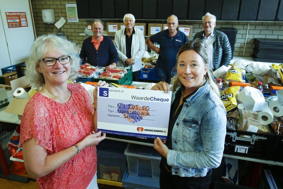 Marleen Vink van Sement reikt de cheque uit aan een medewerker van de Voedselbank Velsen.