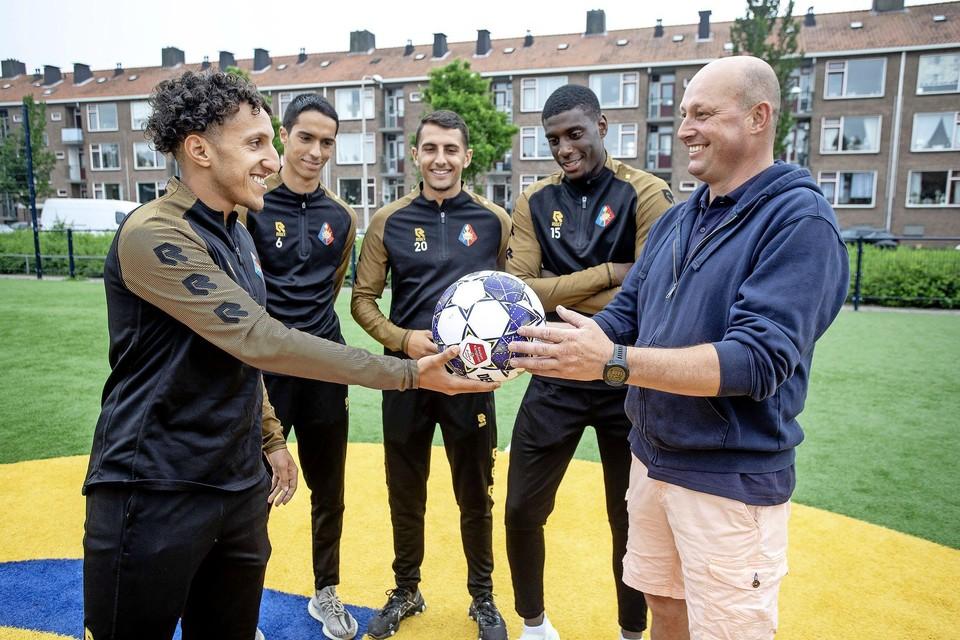Telstar-spelers overhandigen wedstrijdbal aan buurtsportcoach Andres op het Cruijff Court.