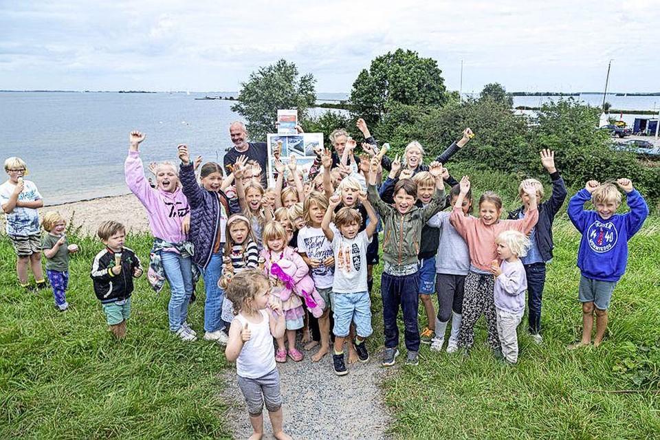 Kinderen uit de wijk De Krijgsman zijn blij met het rapport van Arcadis over de uitbreiding van het strandje achter hen.