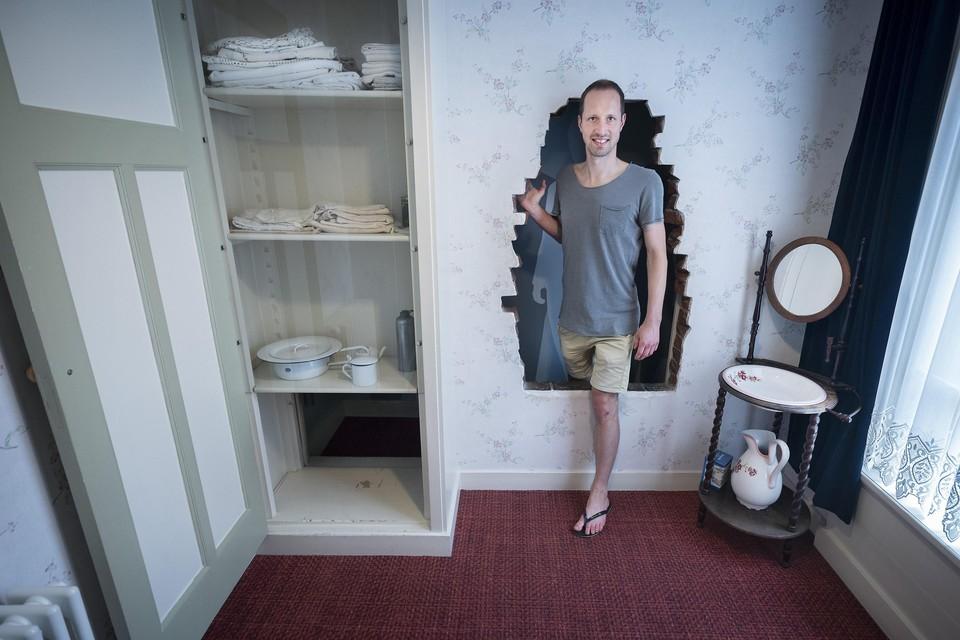 Een bezoeker stapt uit de geheime kamer, waarin onderduikers zich in geval van nood konden verstoppen.