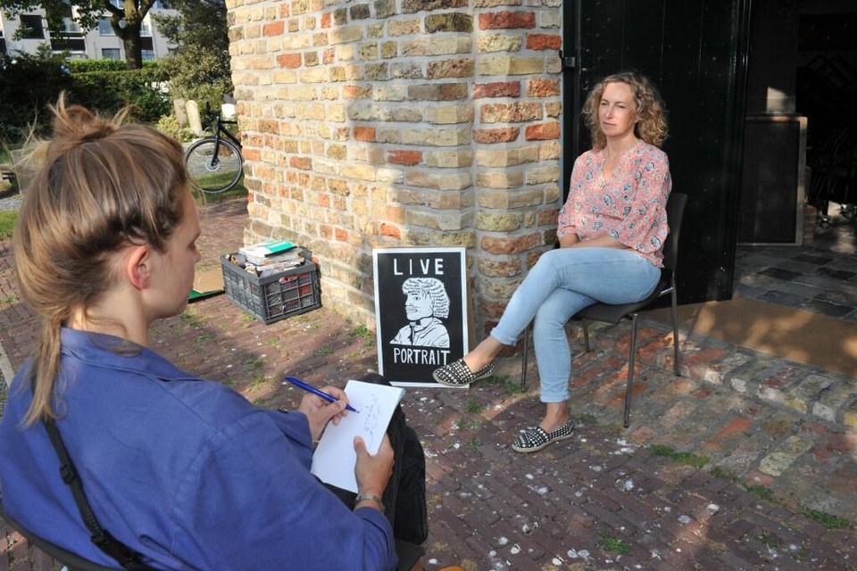 Marieke Luthart is tijdens de tekendag in Heemskerk doende met een portret van Eva Jansen.