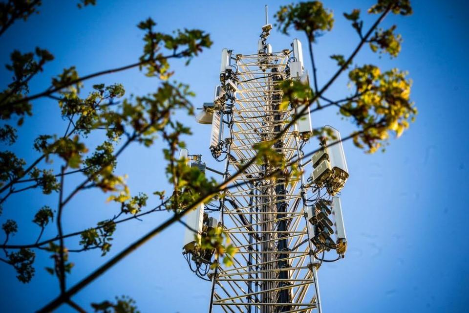 Monteurs aan het werk bij een zendmast voor mobiele netwerken die door een brand zwaar beschadigd is geraakt.