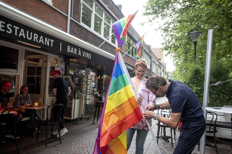 Lotte Godfroy van koffiebar Loco assisteert Patrick van der Vooren van Grand Café Batifol bij het installeren van de regenboogvlag.