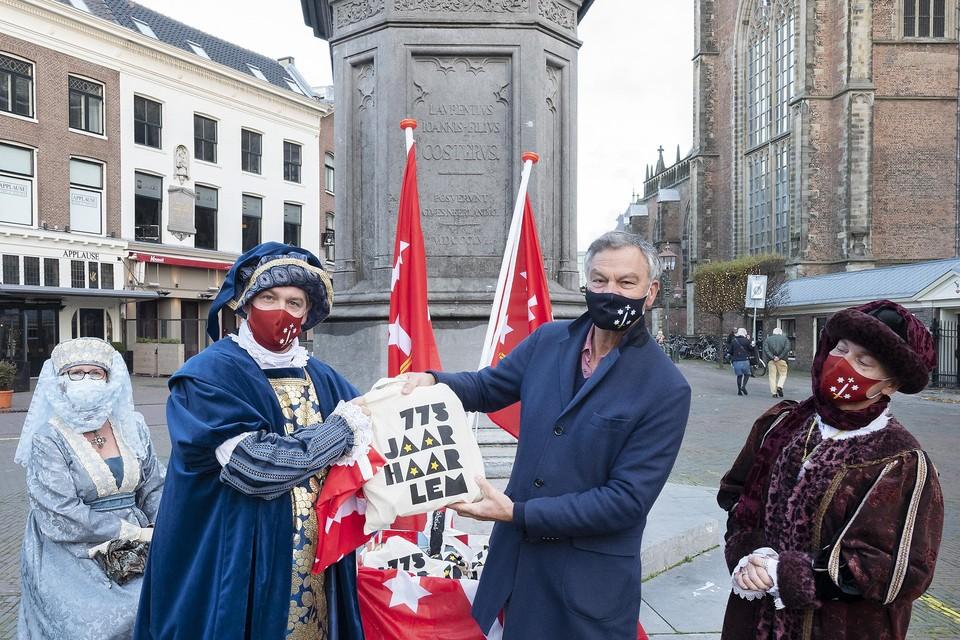 Historische figuren met mondkapjes overhandigen een borreltas aan de voorzitter van de voedselbank Bernt Schneiders.