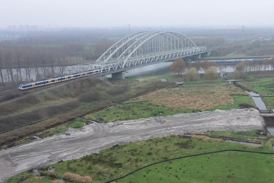 Dronefoto van de spoorbrug over het Amsterdam-Rijnkanaal met op de voorgrond een deel van het zandpakket op het tracé van de toekomstige ontsluitingsweg.