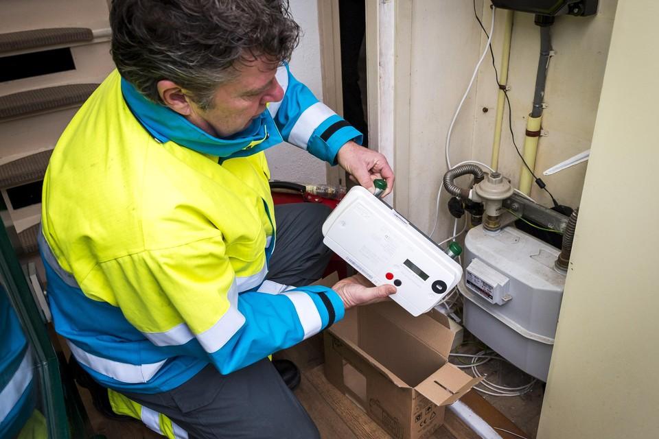 Een monteur installeert een slimme meter.