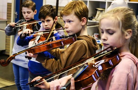 Op de Rozenbeek in Velserbroek krijgen leerlingen vioolles op school: 'De kinderen leren samenwerken. Soms duurt het even voordat zij snappen hoe je samen een orkest moet zijn'