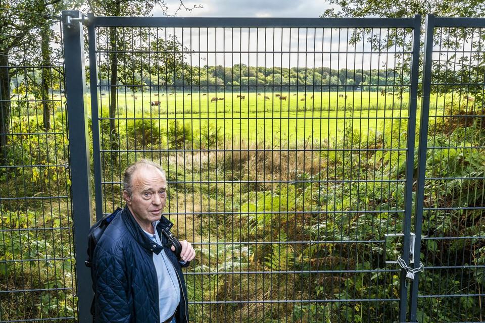 Voormalig boswachter Huub Adank achter het hek in de Amsterdamse Waterleidingduinen. Aan de andere kant van het hek ligt de Vogelenzangse polder met de roodbonte koeien.