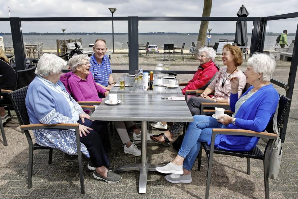 Rik van der Haar op het terras van Aan de Kade met gasten en vrijwilligers van De Zonnebloem, afdeling Huizen.