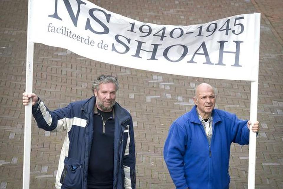 Herman Meerman en Chris Hahn (r.) met het spandoek waarin zij het verleden van de NS in WO II aan de kaak stellen.