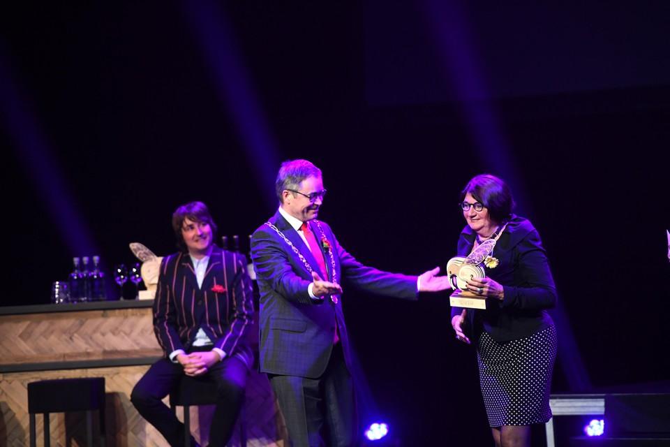 Joke Breemouer ontvangt de juryprijs van burgemeester Jos Wienen. Publieksprijswinnaar Yorick van Norden kijkt op de achtergrond mee.