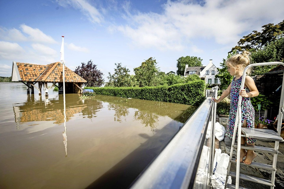 Een meisje bekijkt hoe snel het water van de Maas stijgt bij een tijdelijke waterkering in een tuin in Arcen (Noordoost-Limburg).