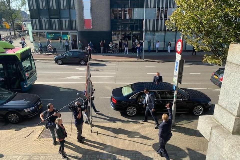 Koning Willem-Alexander zwaait na zijn bliksembezoek nog even snel naar de nieuwsgierige toeschouwers voor hij weer de auto in stapt.