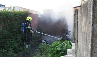Scooter en rolcontainer in brand achter huis in IJmuiden