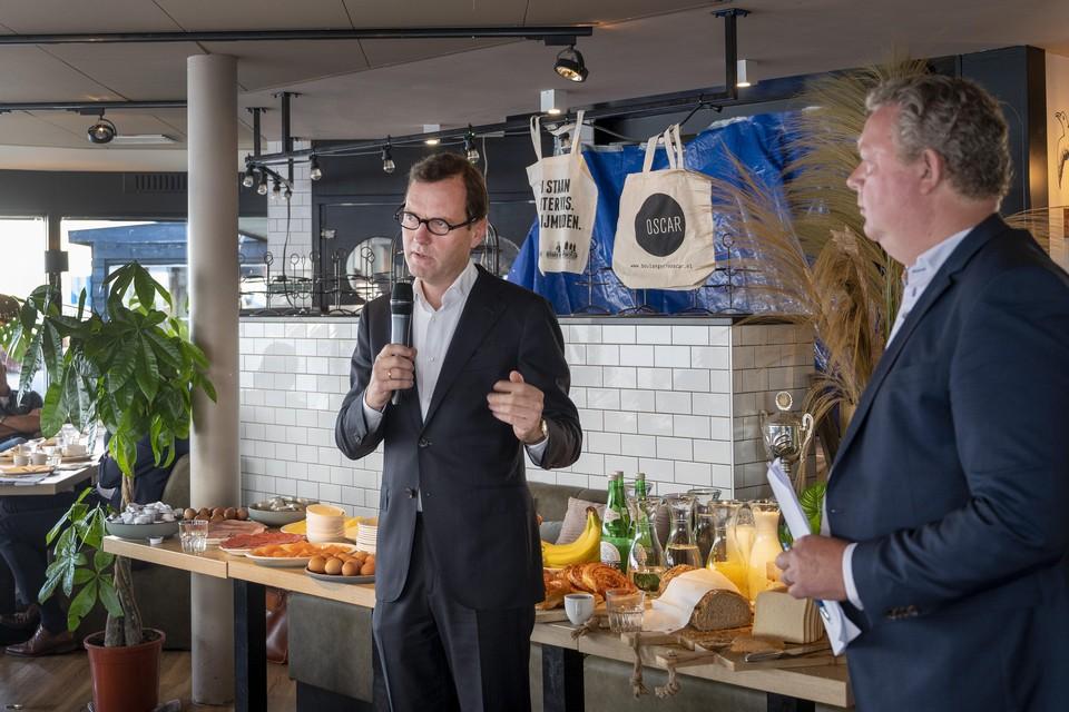 Donald Voskuil voert het woord. IJpos-voorzitter Theo Koster luistert mee.
